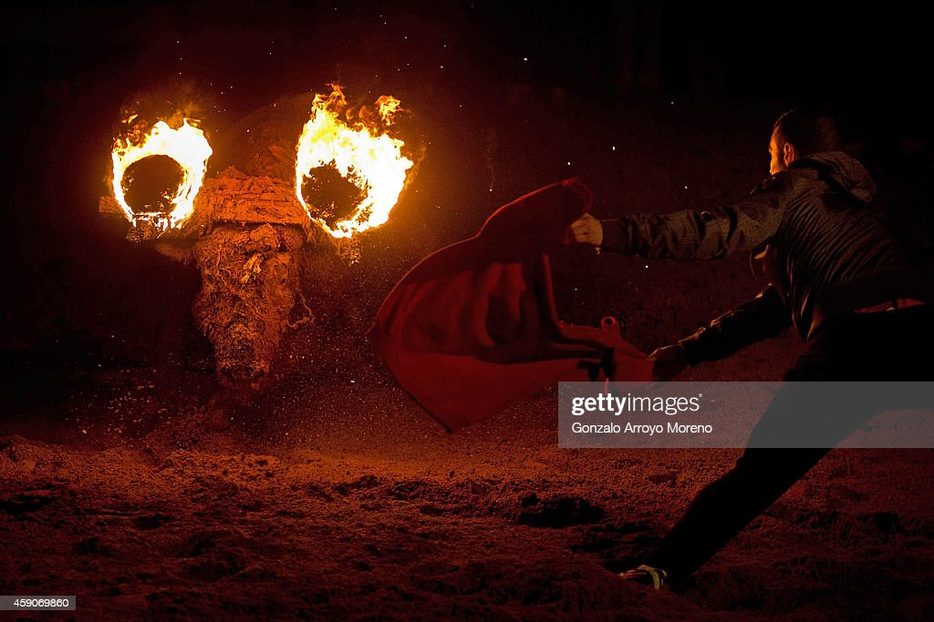 A reveler uses a jersey as a cape ahead of a bull with flammable balls attached to it's horns during the 'Toro de Jubilo' fire bull festival on November 16, 2014 in Medinaceli, Spain. Toro de Jubilo, a Fire Bull festival, is an ancient tradition held annually at midnight in the Spanish town of Medinaceli. The event starts when flammable balls attached to a bull,s horns are set alight. The animal is then untied and revelers dodge it until the flammable material is consumed. The body of the animal is covered with mud to protect it from burns.