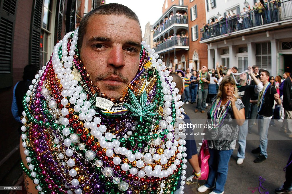 A reveler walks along Bourbon Street with a stack of beads around his neck during Mardi Gras day on February 24 2009 in New Orleans Louisiana The...