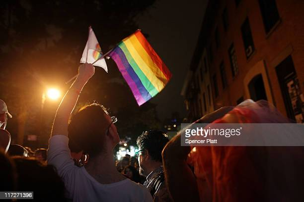 A reveler waves a gay pride flag in front of the historic gay bar The Stonewall after the passing of a bill legalizing gay marriage in New York State...