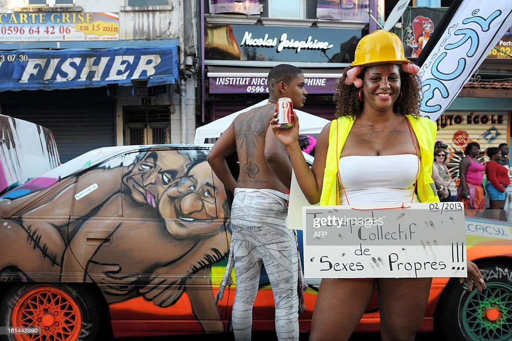 A reveler wearing a sign reading 'public transportation of 'clean sex'!!!' as she stands in front of a car during the Carnival parade in the streets of Fort-de-France on the French Caribbean island of Martinique, on February 10, 2013. The Carnaval started on February 9, 2013 and will run until Ash Wednesday on February 13, 2013 when Vaval, a giant papier-mache figure symbolizing the king of the carnival, is burned.