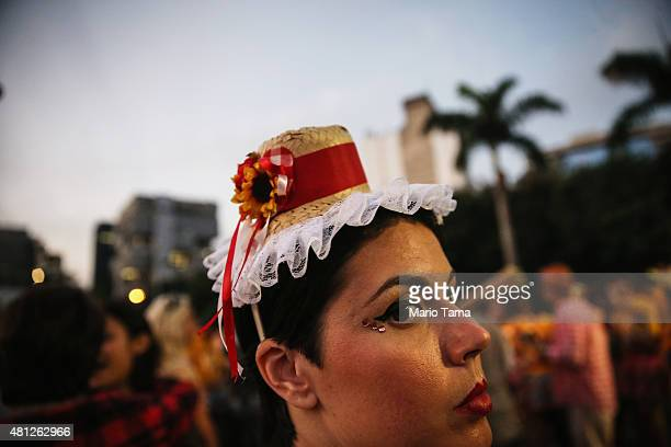 A reveler wears a miniature country hat during a 'Festas Juninas' performance by the street band 'Monobloco' on July 18 2015 in Rio de Janeiro Brazil...