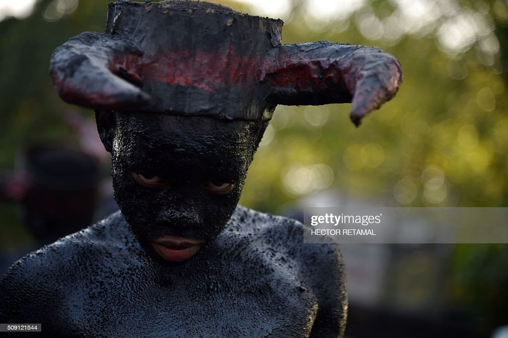 A reveler with body painted in motor oil depicting the devil perform during the 2016 National Carnival Parade on February 9, 2016 in Port-au-Prince, Haiti. The name in Haitian creole of the carnival for this year is 'Ayiti Toutan' (Haiti Always). The launch of the carnival the previous day was suspended due to the political situation affecting Haiti. / AFP / HECTOR RETAMAL