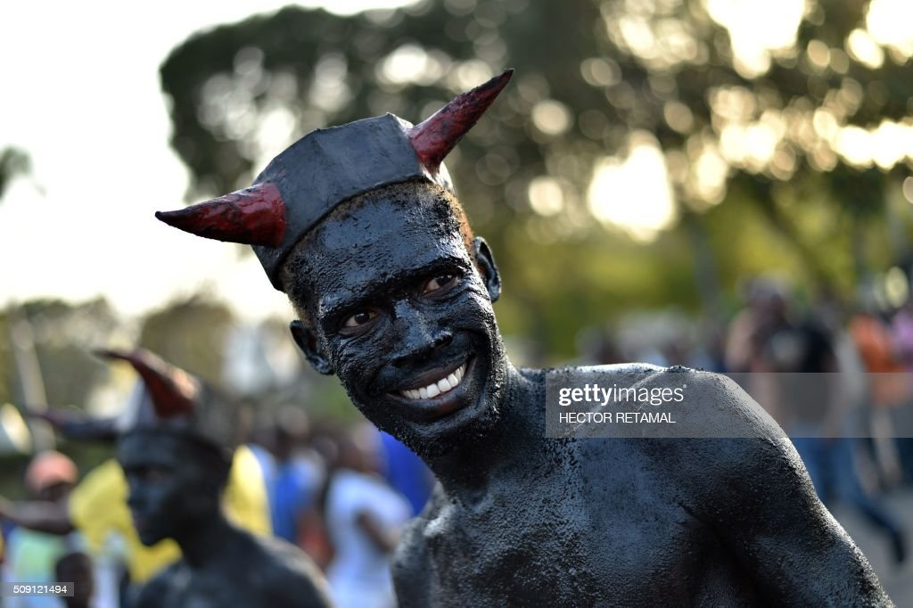 A reveler with body painted in motor oil depicting the devil performs during of 2016 National Carnival Parade on February 9, 2016, in Port-au-Prince, Haiti. The name of the carnival for this year is Ayiti Toutan, in Haitian creole,(Haiti always). Yesterday was suspended the first day of carnival by the political situation affecting Haiti. The name in Haitian creole of the carnival for this year is 'Ayiti Toutan' (Haiti Always). The launch of the carnival the previous day was suspended tdue to the political situation affecting Haiti. / AFP / HECTOR RETAMAL