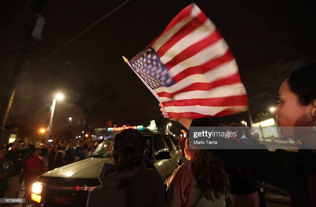 Revelers applaud and cheer as motorists pass at an impromptu celebration following the successful operation to capture 19-year-old bombing suspect Dzhokhar A. Tsarnaev on April 19, 2013 in Watertown, Massachusetts. A manhunt for a suspect in the Boston Marathon bombing, Dzhokhar A. Tsarnaev, 19, ended this evening with his capture on a boat parked on a residential property in Watertown, Massachusetts. His brother Tamerlan Tsarnaev, 26, the other suspect, was shot and killed by police early this morning after a car chase and shootout with police. The two men are suspects in the bombings at the Boston Marathon on April 15 that killed three people and wounded at least 170.