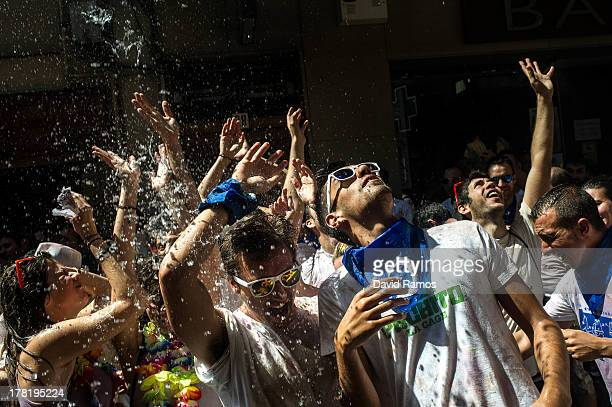 Revelers are sprayed with water thrown from balconies after the CIpotegato run through the streets on August 27 2013 in Tarazona Spain Every year...