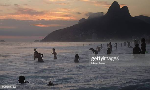Revelers bathe on Ipanema beach at sunset during Carnival celebrations on February 7 2016 in Rio de Janeiro Brazil Festivities have continued...