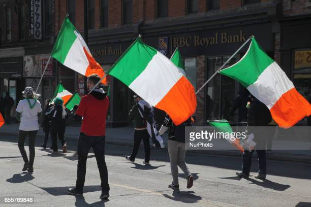 Revelers carrying the flag of Ireland during the St Patrick's Day Parade in Toronto Ontario Canada on March 19 2017