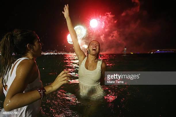 Revelers celebrate as fireworks explode during New Year's festivities on Copacabana Beach on January 1 2015 in Rio de Janeiro Brazil Up to 2 million...