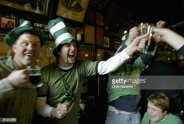 Revelers clink beer glasses and enjoy themselves during an all day party at historic McSorley's Old Ale House March 17 2004 in New York New Yorkers...
