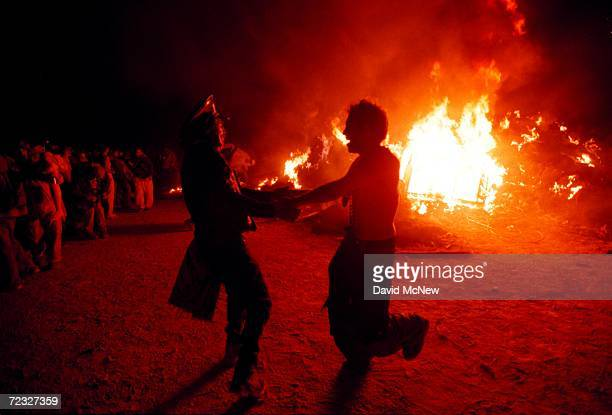 Revelers dance around the burning remains of a 52foot tall wooden man during the 15th annual Burning Man festival September 2 2000 in the Black Rock...