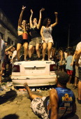 Revelers dance atop a destroyed car at a street party thrown one block away from Rio's main red light district Vila Mimosa on January 5 2014 in Rio...