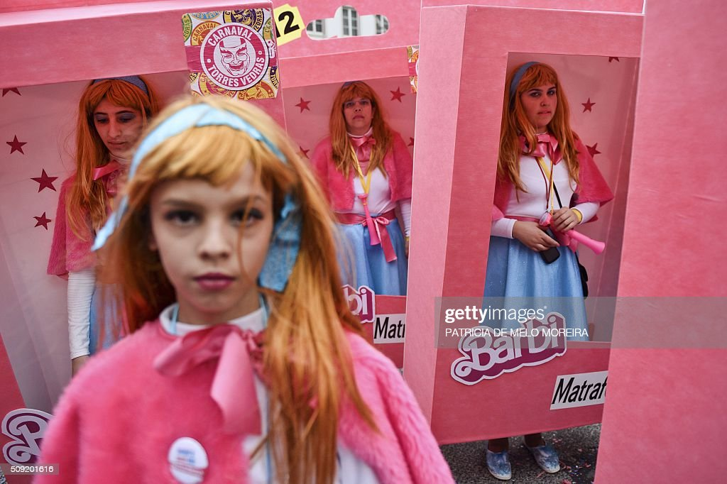 Revelers dressed as 'Barbi' dolls in their boxes participate in the annual carnival parade in Torres Vedras on February 9, 2016. The Torres Vedras Carnival is allegedly the 'most Portuguese' of all the carnivals in the country recognized by the strong political and football satire of the revelers disguises and their floats. / AFP / PATRICIA DE MELO MOREIRA