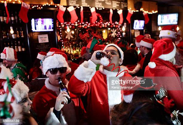 Revelers dressed as Santa Claus drink inside at a bar in the East Village neighborhood during the annual SantaCon bar crawl event on December 14 2013...