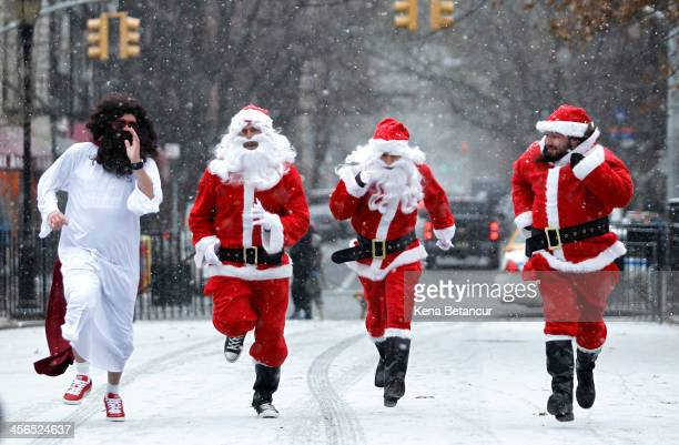 Revelers dressed as Santa Claus run as the arrive at Tompkins Square Park to take part during the annual SantaCon bar crawl event on December 14 2013...