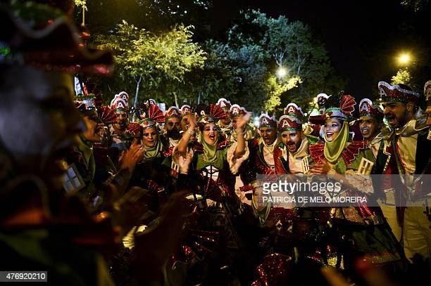 Revelers from one of Lisbon's neighborhoods Alfama gather moments after performing at the Saint Anthony's Parade on Avenida da Liberdade in Lisbon on...