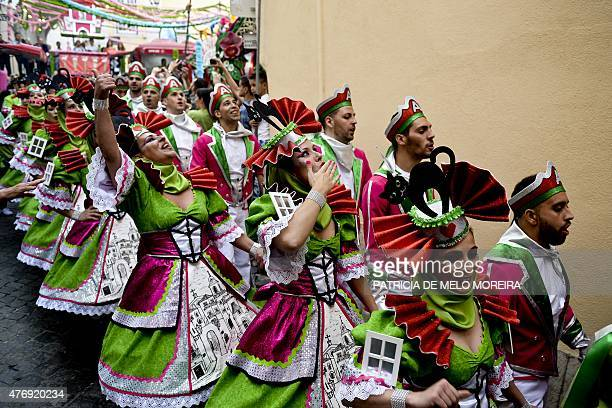 Revelers from one of Lisbon's neighborhoods Alfama walk down a street on their way to the Saint Anthony's Parade on Avenida da Liberdade in Lisbon on...