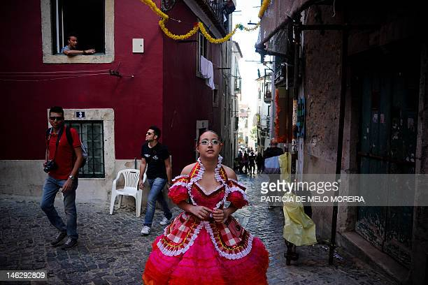 A revelers from the typical Lisbon neighborhood Alfama walks in costuem on her way to the Saint Anthony's Parade on Avenida da Liberdade in Lisbon on...