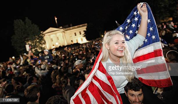 Revelers gather at the fence on the north side of the White House pose for photographs chant 'USA USA' and sing the Star Spangled Banner while US...