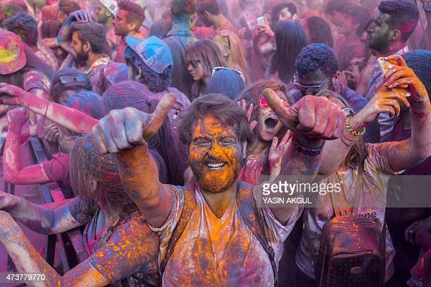 Revelers gesture as they take part in the color festival on May 17 in Istanbul AFP PHOTO/YASIN AKGUL