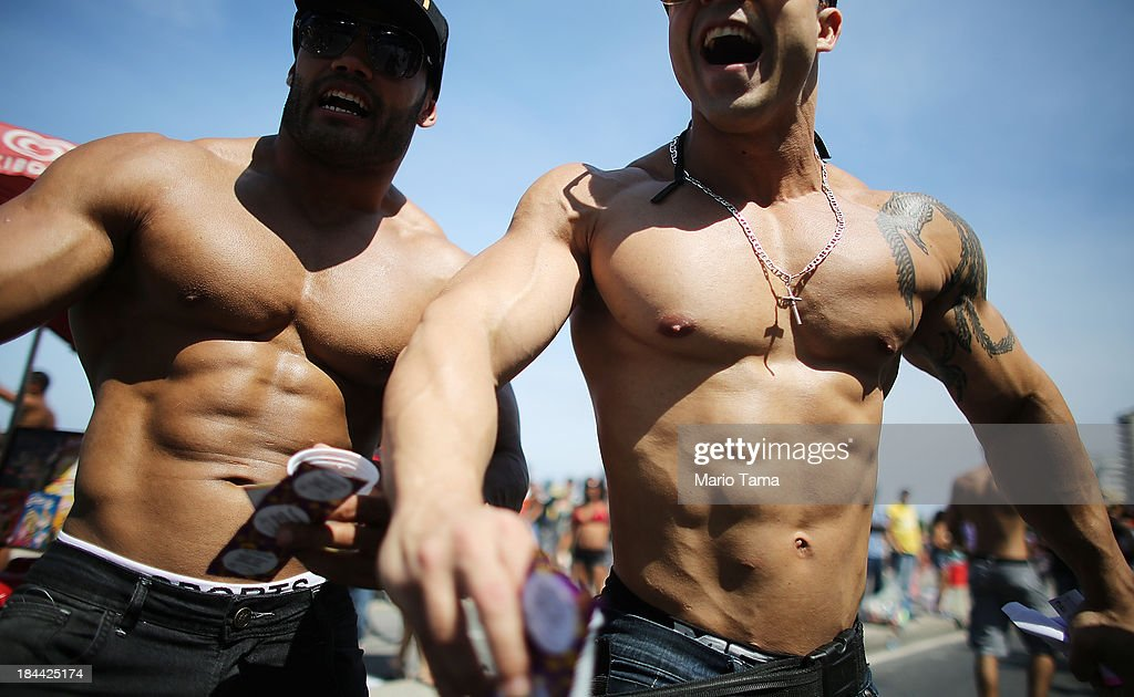 Revelers laugh while flexing during Rio de Janeiro's 18th Gay Pride Parade along Copacabana Beach on October 13, 2013 in Rio de Janeiro, Brazil. Brazil is the world's largest Catholic nation with an estimated 60,000 gay couples. In May, Brazil became the third country in Latin America to effectively approve same-sex marriage via a court ruling, but a final law has yet to be passed.
