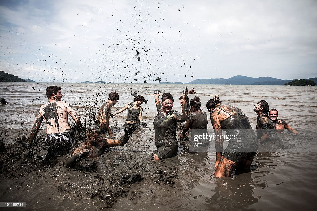 Revelers participate in the traditional Bloco da Lama (Mud block) carnival in Parati, Rio de Janeiro State, Brazil, on February 9, 2013. The event, which was begun by two men in a playful manner in 1986, has now become a traditional carnival in which participants disguised as primitives with rags, lianas or skulls and bones, dive in the mud. AFP PHOTO/Victor MORIYAMA