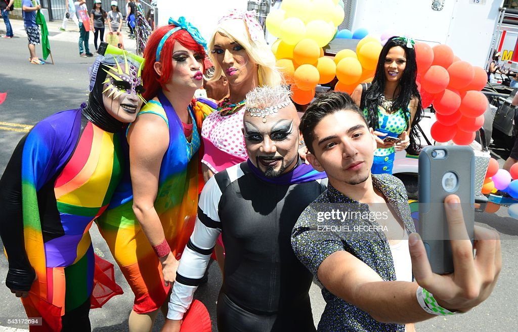 Revelers pose for a selfie as they take part in the Gay Pride Parade in San Jose on June 26, 2016. / AFP / Ezequiel Becerra