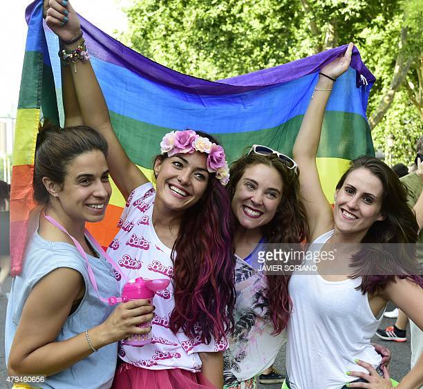Revelers pose with a rainbow flag during the annual Gay Pride Parade in Madrid on July 4 2015 AFP PHOTO/ JAVIER SORIANO