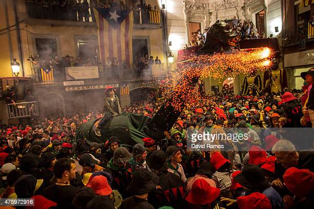 Revelers run away from the 'Guita Gran' big dragon in Catalan as it emits sparks during the first day of 'La Patum' Festival on June 4 2015 in Berga...