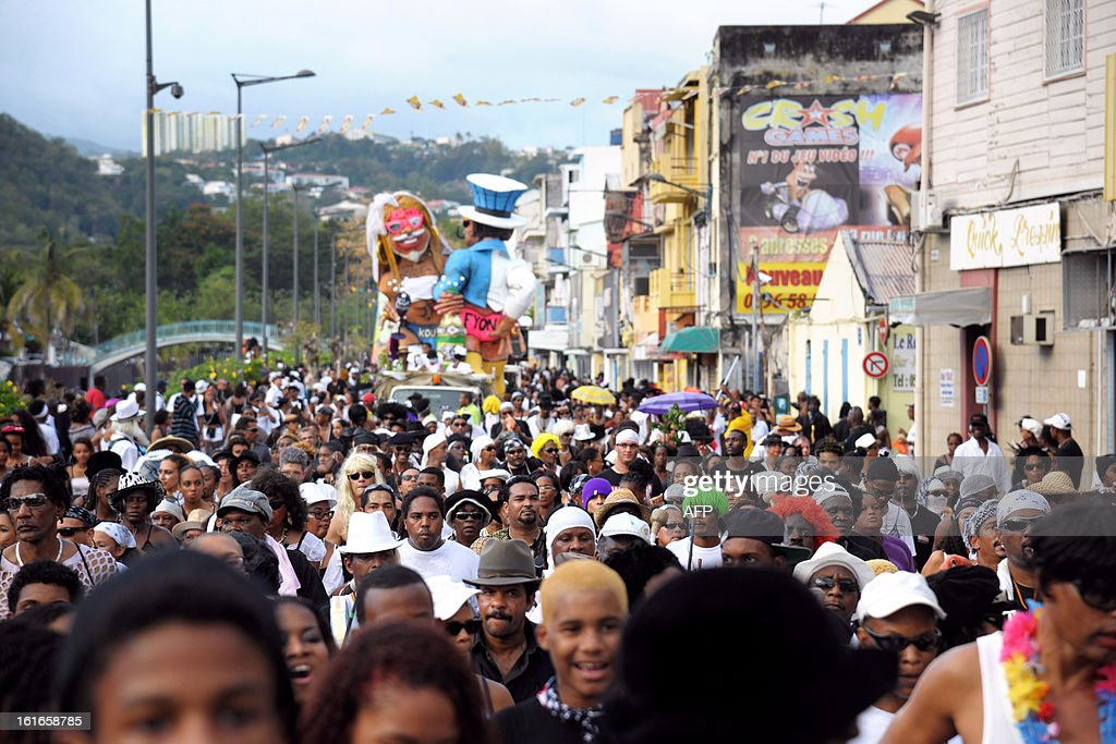 Revelers suround papier-mache figures, dressed-up in wedding costumes, representing King Vaval and mocking France's right-wing opposition UMP leader Jean-Francois Cope and former Prime minister Francois Fillon parade before being burnt at the end of the Carnival parade in Fort-de-France on the French Caribbean island of Martinique, on February 14, 2013.