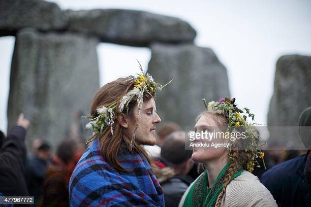 Revelers take part in celebrations to mark the summer solstice at Stonehenge prehistoric monument on June 21 2015 in Wiltshire England Thousands of...