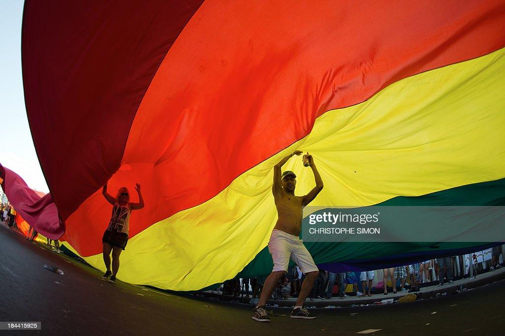 Revelers take part in the gay pride parade at Copacabana beach in Rio de Janeiro, Brazil on October 13, 2013. AFP PHOTO / CHRISTOPHE SIMON