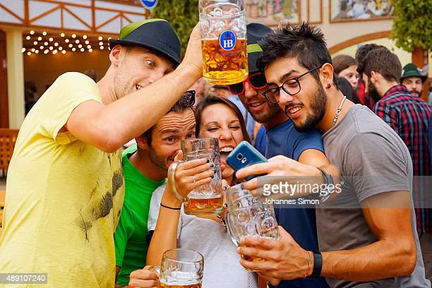 Revelers take photos as they drink beer at Hofbraeuhaus beer tent on the opening day of the 2015 Oktoberfest on September 19 2015 in Munich Germany...