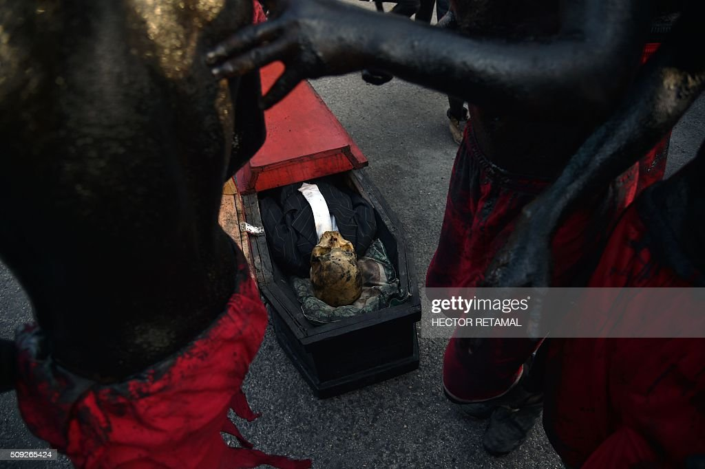 Revelers, their bodies painted with a mixture of cane sugar syrup and coal depicting the devil circle a coffin during the 2016 National Carnival Parade on February 10, 2016 in Port-au-Prince, Haiti. The name in Haitian creole of the carnival for this year is 'Ayiti Toutan' (Haiti Always). The launch of the carnival two days ago was postponed due to the political situation affecting Haiti. / AFP / HECTOR RETAMAL