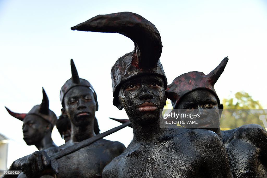 Revelers, their bodies painted with a mixture of cane sugar syrup and coal depicting the devil, perform during the 2016 National Carnival Parade on February 10, 2016 in Port-au-Prince, Haiti. The name in Haitian creole of the carnival for this year is 'Ayiti Toutan' (Haiti Always). The launch of the carnival two days ago was postponed due to the political situation affecting Haiti. / AFP / HECTOR RETAMAL