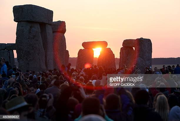 Revelers watch as the sun rises over the standing stones at the prehistoric monument Stonehenge near Amesbury in Southern England on June 21 as...