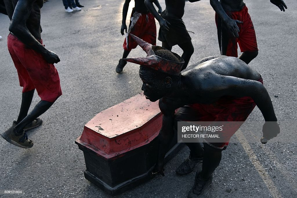 Revelers with body painted in motor oil depicting the devil run around a coffin during the 2016 National Carnival Parade on February 9, 2016 in Port-au-Prince, Haiti. The name in Haitian creole of the carnival for this year is 'Ayiti Toutan' (Haiti Always). The launch of the carnival the previous day was suspended due to the political situation affecting Haiti. / AFP / HECTOR RETAMAL