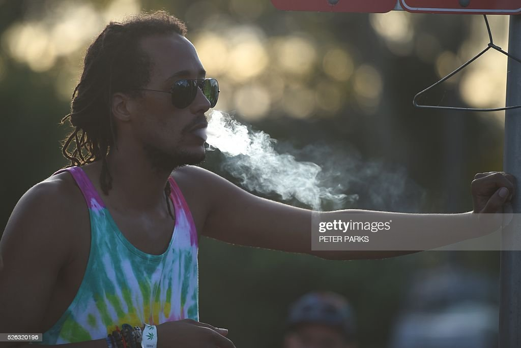 A reveller at the Mardi Grass festival smokes during the Global Marijuana March in the eastern Australian town of Nimbin on April 30, 2016. . The festival, an annual cannabis law reform protest and gathering, attracts thousands of revellers from across Australia and around the world. / AFP / PETER