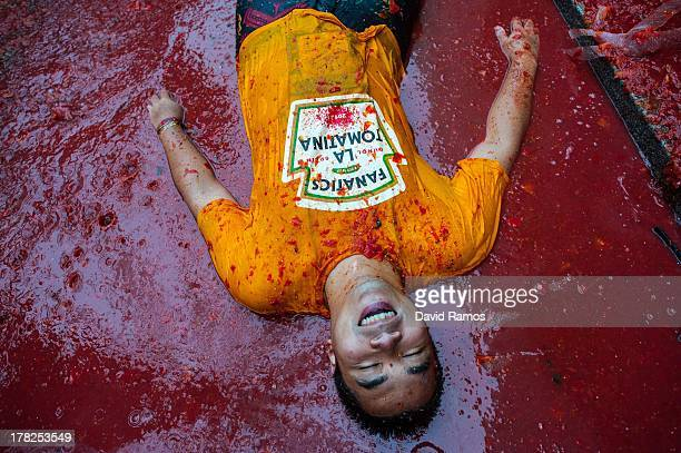 A reveller baths in tomato pulp while participating the annual Tomatina festival on August 28 2013 in Bunol Spain An estimated 20000 people threw 130...