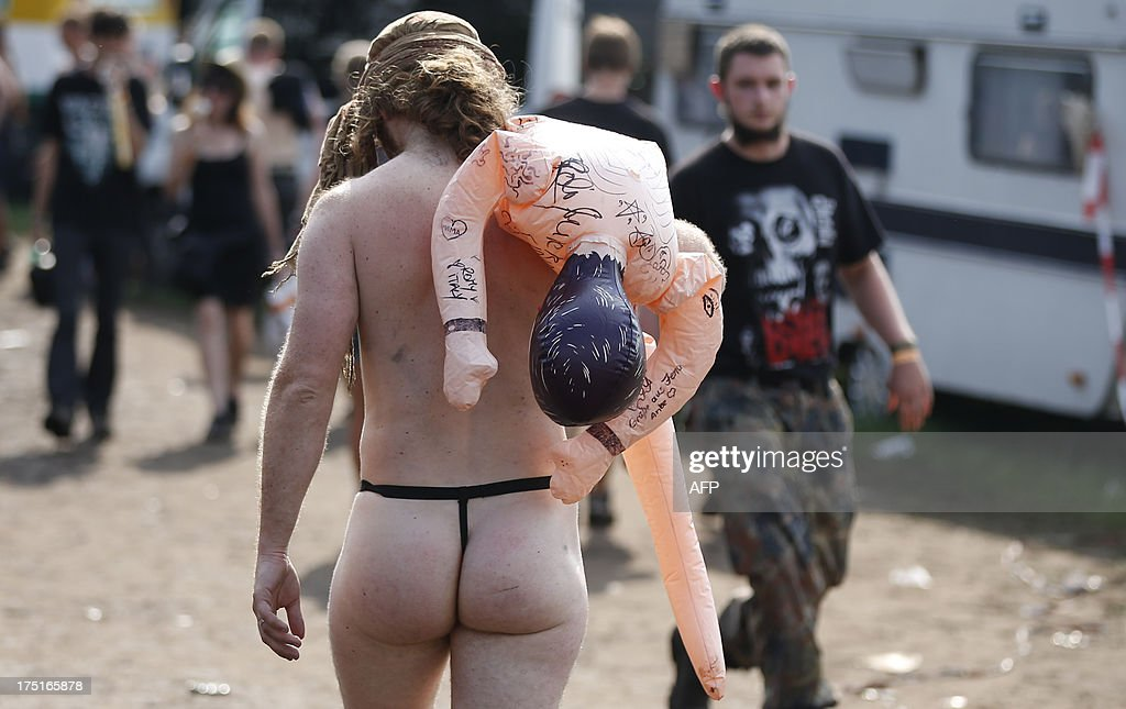 A reveller carries a deflated sex-doll during the 24th heavy metal Wacken Open Air (WOA) Festival 2013 in Wacken, northern Germany on August 1, 2013. With some 80,000 festival visitors it attracts all kinds of metal music fans, such as fans of black metal, death metal, power metal, thrash metal, gothic metal, folk metal and even metalcore, nu metal and hard rock from around the world.