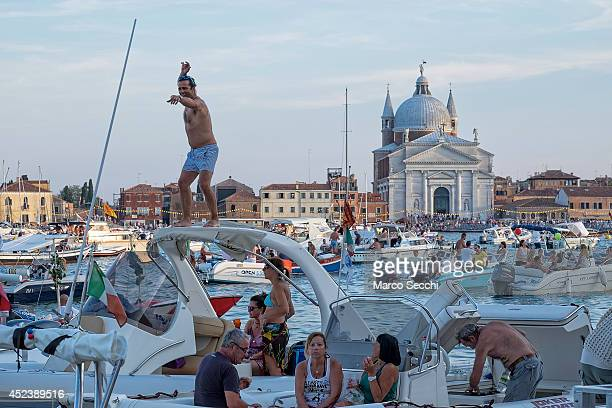 A reveller dance on top of his power boat with the background of the Redentore Church on July 19 2014 in Venice Italy Redentore which is in...
