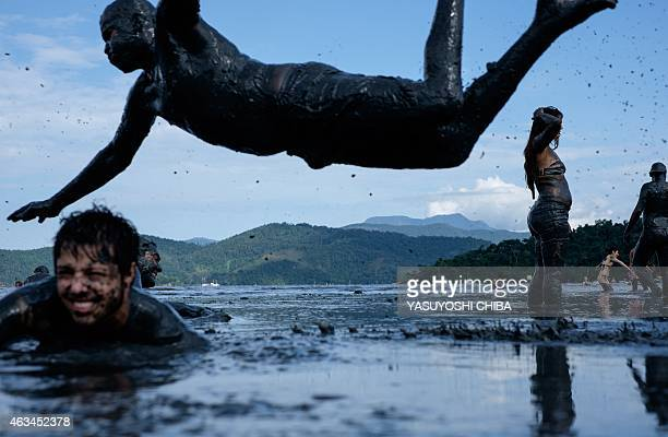A reveller dives to prepare for 'Bloco da Lama' a mud carnival in Paraty about 250km south of Rio de Janeiro Brazil on February 14 2015 'Bloco da...