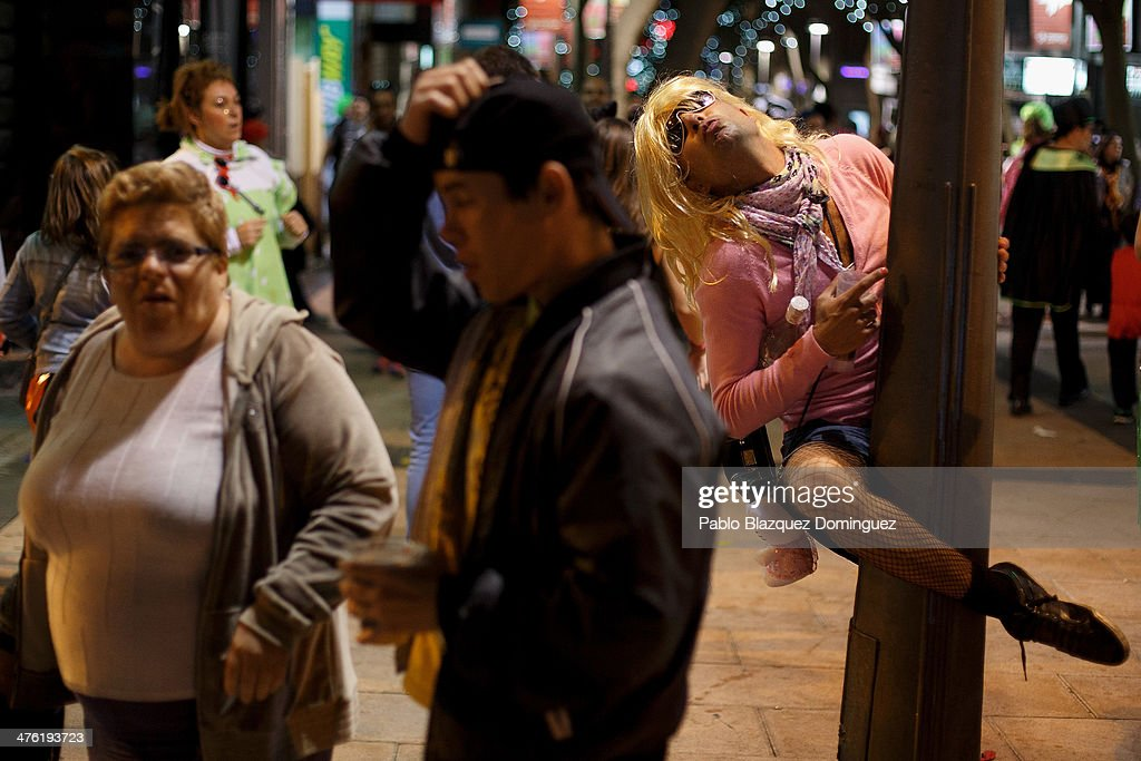 A reveller dressed as a woman grabs to a lamp post during during the Santa Cruz de Tenerife Carnival on March 2 2014 in Santa Cruz de Tenerife on the...