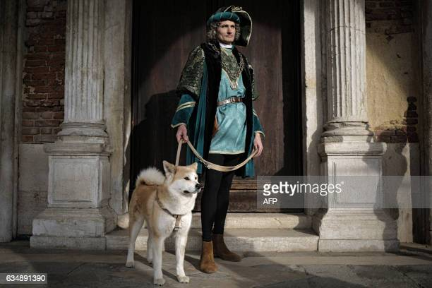 A reveller dressed in mask and period costume with a dog on a leash takes part in the Venice Carnival on February 12 2017 in Venice / AFP / Marco...