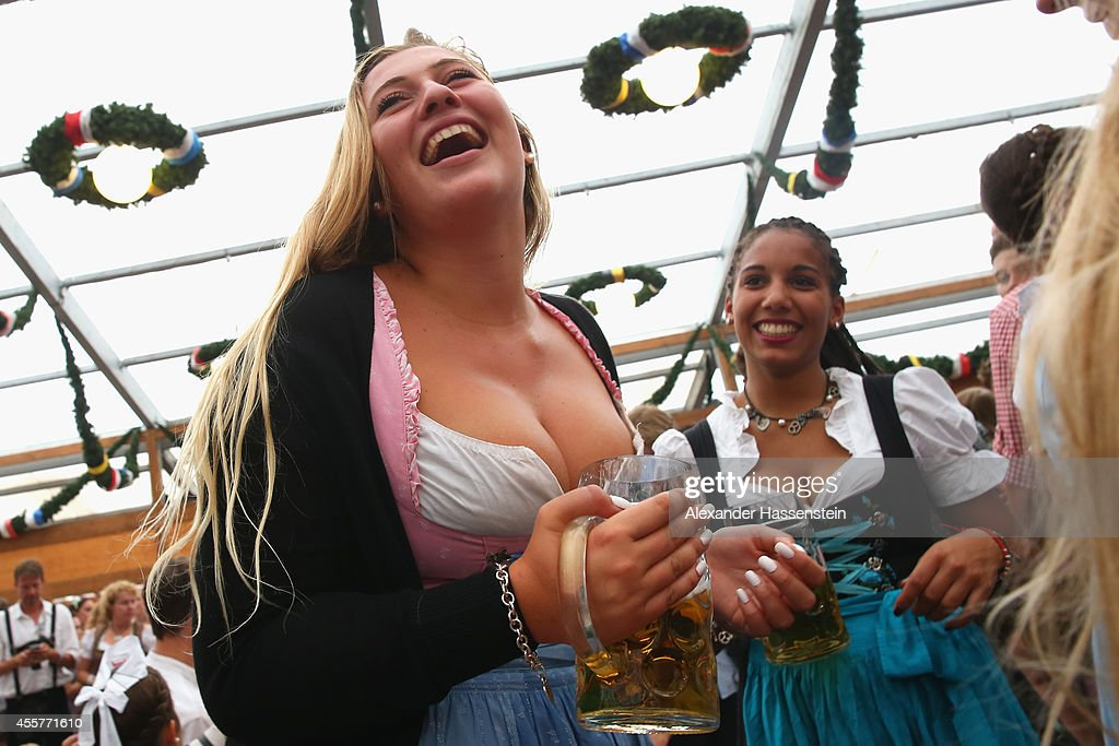 A reveller dressed in traditional Bavarian clothing `Dirndl` holds a beer mug at Schottenhamel beer tent during the opening day of the 2014...