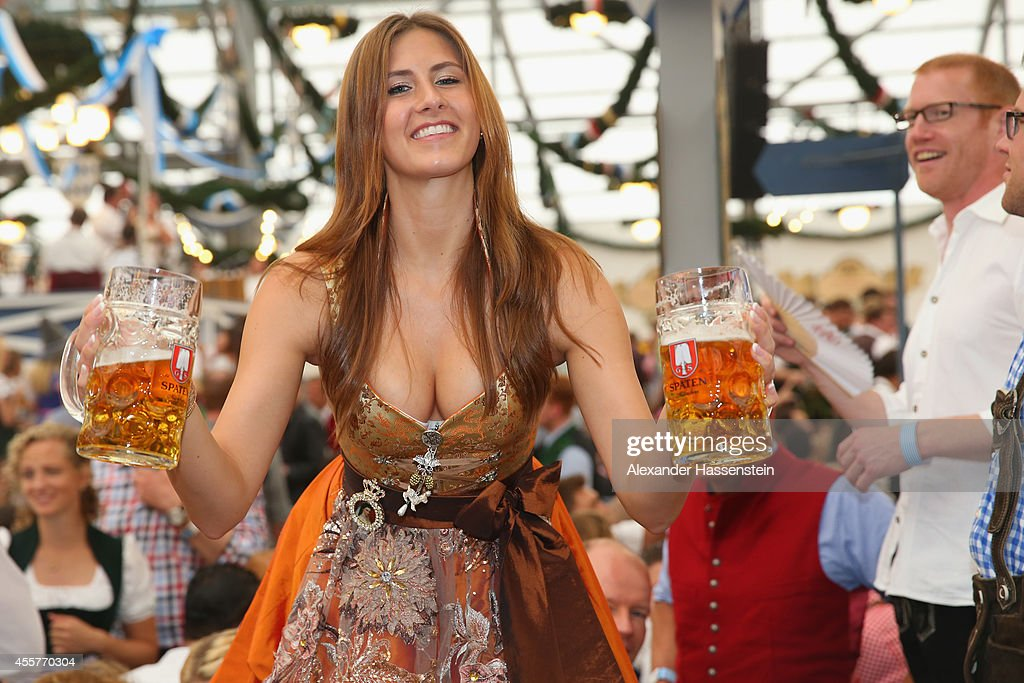 A reveller dressed in traditional Bavarian clothing `Dirndl` holds beer mugs at Schottenhamel beer tent at the opening day of the 2014 Oktoberfest at...
