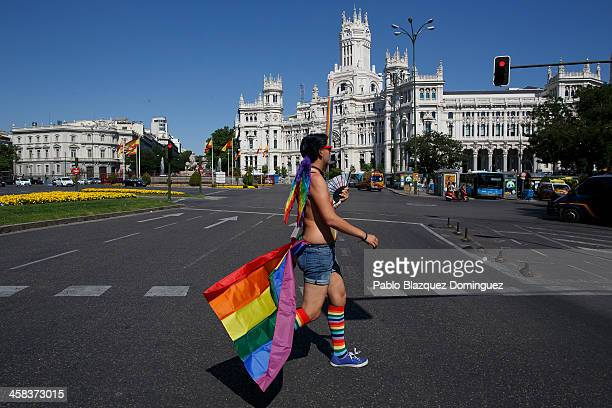 A reveller dressed with the raimbow or gay pride flag walks the streets next to Cibeles Square before the Pride Parade during the Madrid Gay Pride...