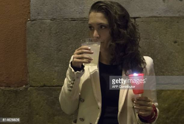 A reveller drinks as she holds a candle after the singing of 'Pobre de Mi' which marks the end of the San Fermin festival in Pamplona early on July...