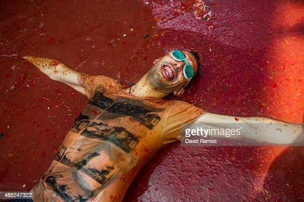 A reveller enjoys the atmosphere in tomato pulp while participating the annual Tomatina festival on August 26 2015 in Bunol Spain An estimated 22000...