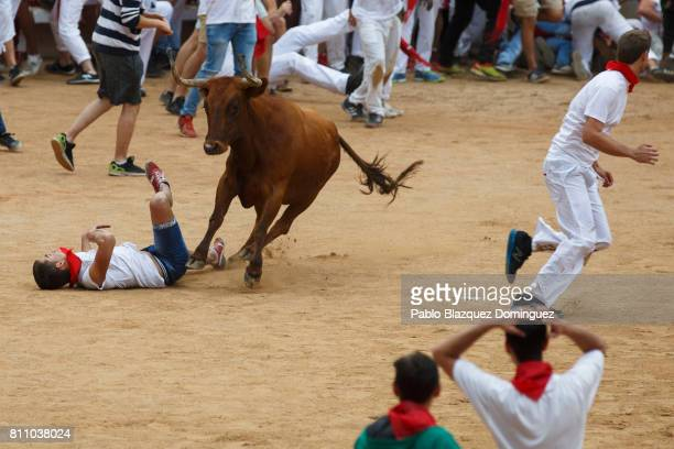 A reveller falls after fainting after being tossed by a heifer in the bullring during the fourth day of the San Fermin Running of the Bulls festival...