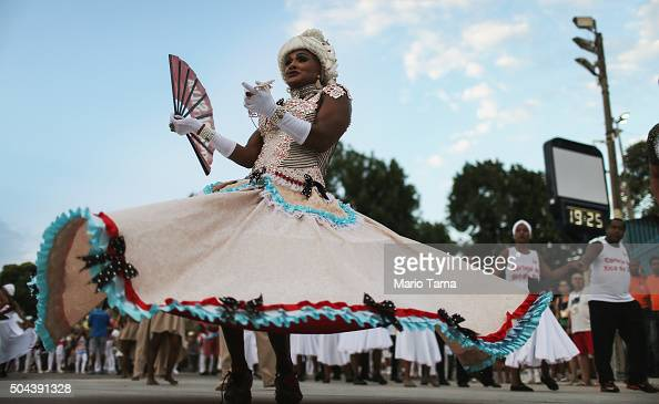 A reveller from the Inocentes de Belford Roxo samba school dances while preparing to march during a preCarnival rehearsal at the Sambodrome on...